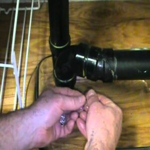 Old plumber retrieves jewelry out of a basin drain.